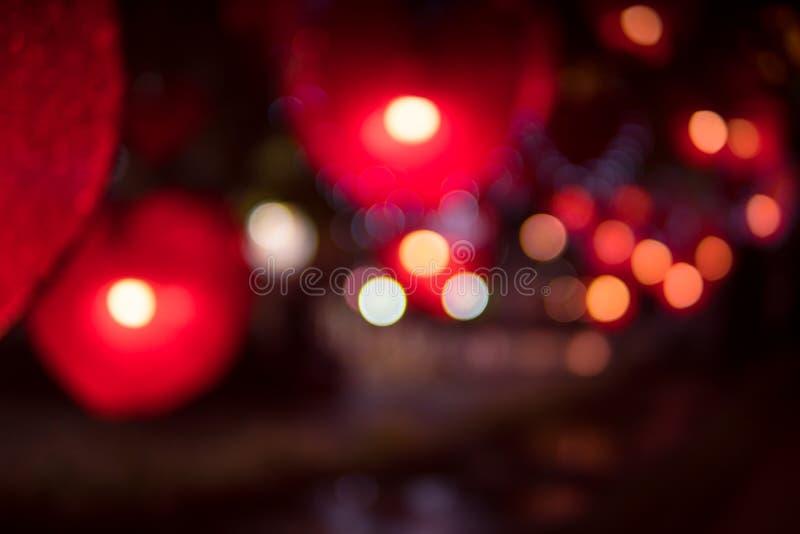 Η ελαφριά θαμπάδα νύχτας πόλεων bokeh, το κόκκινο ελαφρύ υπόβαθρο καρδιών στοκ φωτογραφία