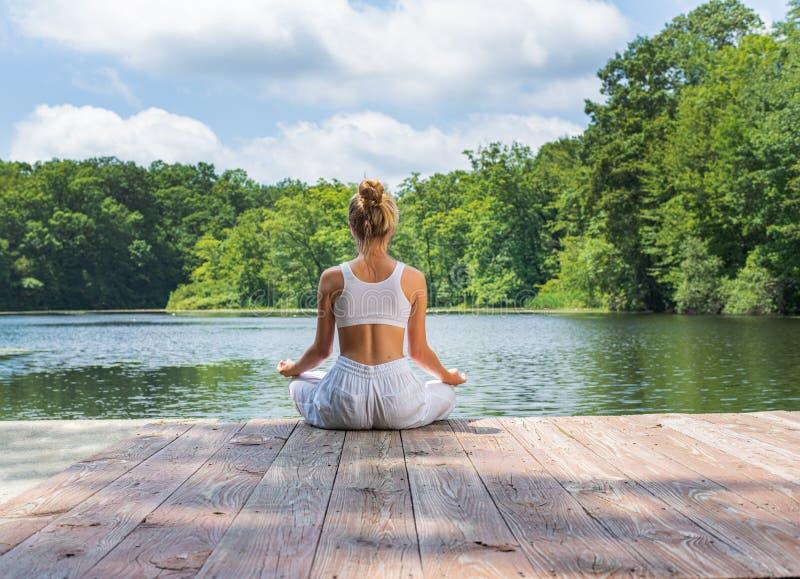 Η ελκυστική γυναίκα ασκεί τη γιόγκα και η περισυλλογή, που κάθεται στο λωτό θέτει κοντά στη λίμνη το πρωί στοκ φωτογραφίες