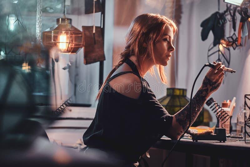 Η ελκυστική γυναίκα κάνει τη συγκόλληση στο χειροτεχνικό στούντιο λαμπτήρων της στοκ εικόνες