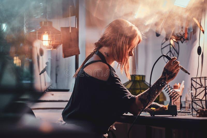 Η ελκυστική γυναίκα κάνει τη συγκόλληση στο χειροτεχνικό στούντιο λαμπτήρων της στοκ εικόνα με δικαίωμα ελεύθερης χρήσης