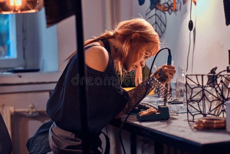 Η ελκυστική γυναίκα κάνει τη συγκόλληση στο χειροτεχνικό στούντιο λαμπτήρων της στοκ εικόνες με δικαίωμα ελεύθερης χρήσης