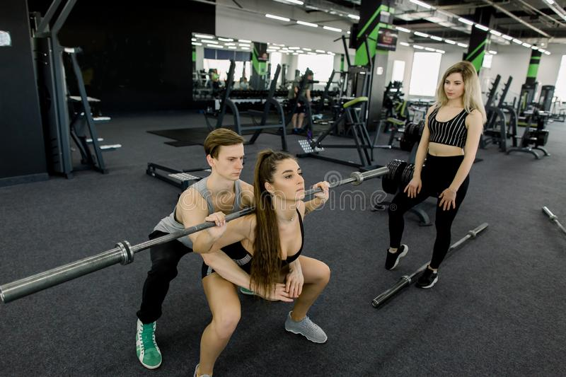 Η ελκυστική γυναίκα και ο όμορφος μυϊκός εκπαιδευτής ανδρών εκπαιδεύουν με τα barbells στην ελαφριά σύγχρονη γυμναστική Όμορφο κο στοκ φωτογραφίες με δικαίωμα ελεύθερης χρήσης
