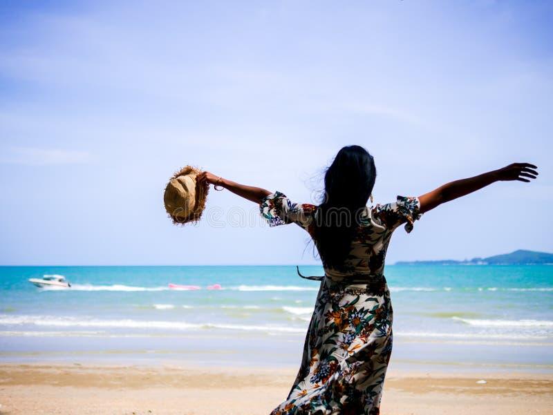 Η ελκυστική γυναίκα που φορά τα εκλεκτής ποιότητας ενδύματα που κρατούν το καπέλο διαθέσιμο και τεντώνει τα όπλα στην ακτή στοκ φωτογραφία