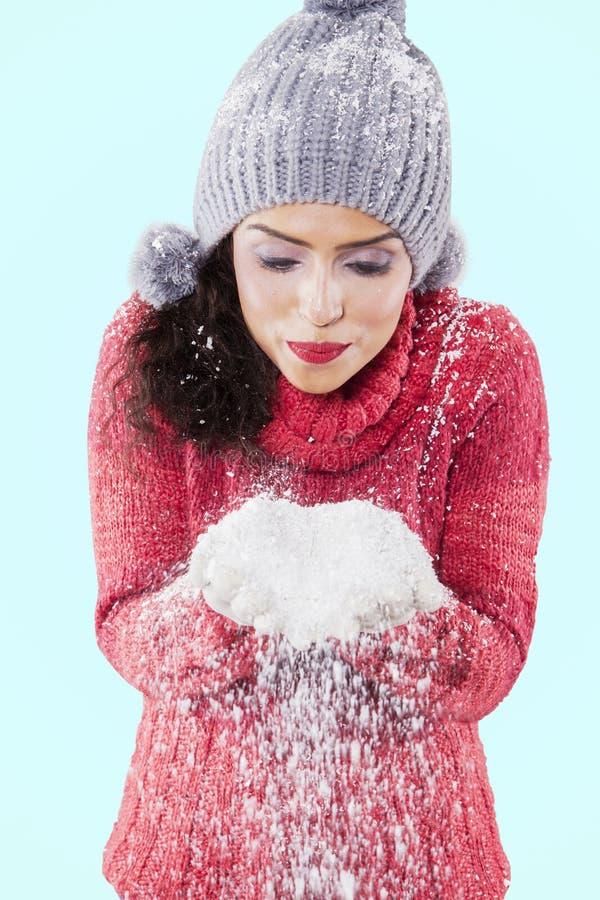 Η ελκυστική γυναίκα φυσά το χιόνι από τα χέρια της στοκ εικόνα με δικαίωμα ελεύθερης χρήσης