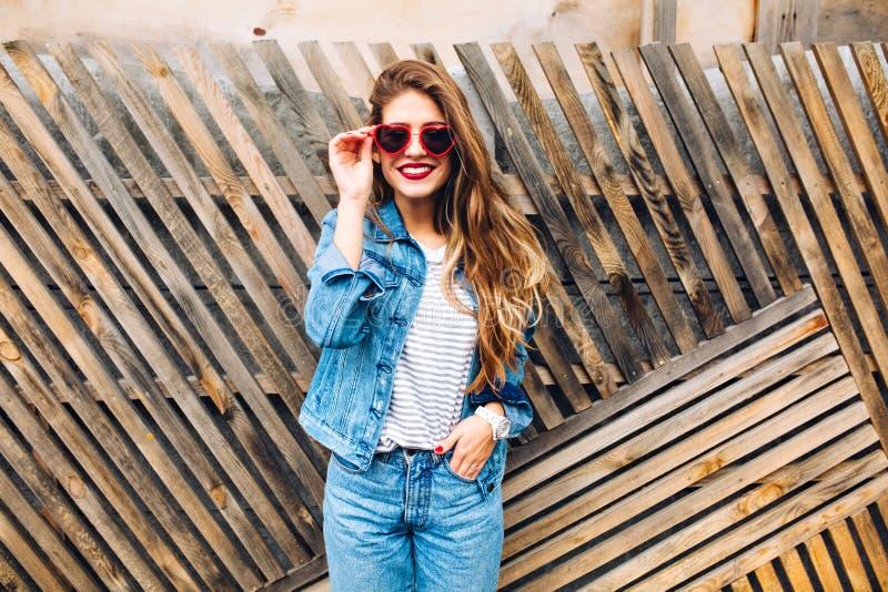 Η ελκυστική θηλυκή πρότυπη μόνιμη τοποθέτηση με παραδίδει την τσέπη σε ένα ξύλινο υπόβαθρο Γοητευτικός το χαμογελώντας κορίτσι μέ στοκ εικόνες
