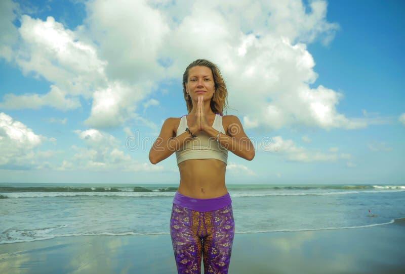 Η ελκυστική και ευτυχής αθλητική γυναίκα στην όμορφη παραλία στη γιόγκα θέτει συγκεντρωμένος και που χαλαρώνει κάνοντας την άσκησ στοκ φωτογραφία με δικαίωμα ελεύθερης χρήσης