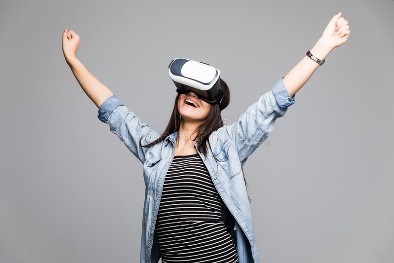 Η ελκυστική και ευτυχής γυναίκα που χρησιμοποιεί τα προστατευτικά δίοπτρα εικονικής πραγματικότητας γιορτάζει τη χειρονομία νίκης στοκ φωτογραφία με δικαίωμα ελεύθερης χρήσης