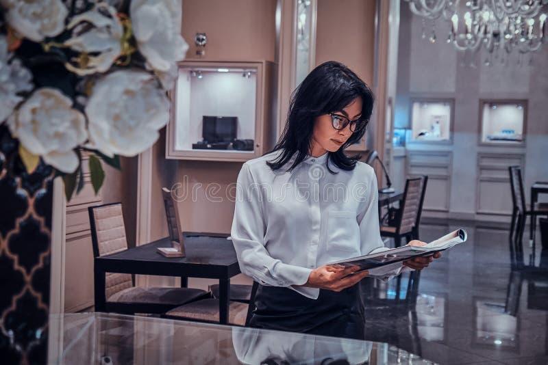 Η ελκυστική κομψή γυναίκα προσέχει το περιοδικό στην κομψή μπουτίκ κοσμημάτων στοκ φωτογραφία