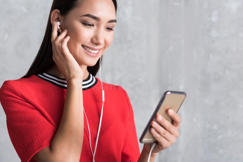 Η ελκυστική νέα γυναίκα επιλέγει το αγαπημένο τραγούδι στοκ εικόνες