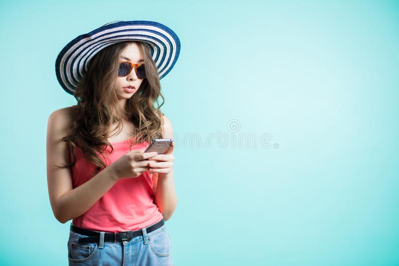 Η ελκυστική νέα γυναίκα στο καπέλο που εξετάζει το έξυπνο τηλέφωνό της και διαβάζει το μήνυμα με τα σοβαρά πρόσωπα στοκ εικόνες