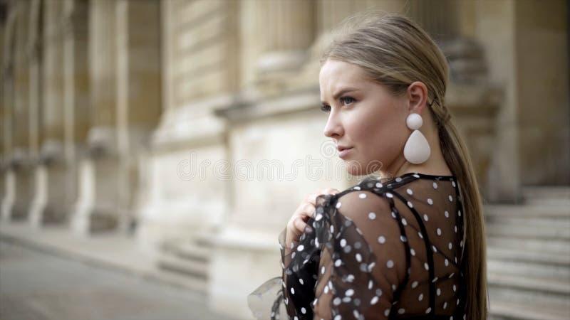 Η ελκυστική νέα γυναίκα φαίνεται γοητευτική στο υπόβαθρο του παλαιού κτηρίου r Ξανθή προκλητική εξέταση πέρα από τον ώμο τη κάμερ στοκ εικόνες