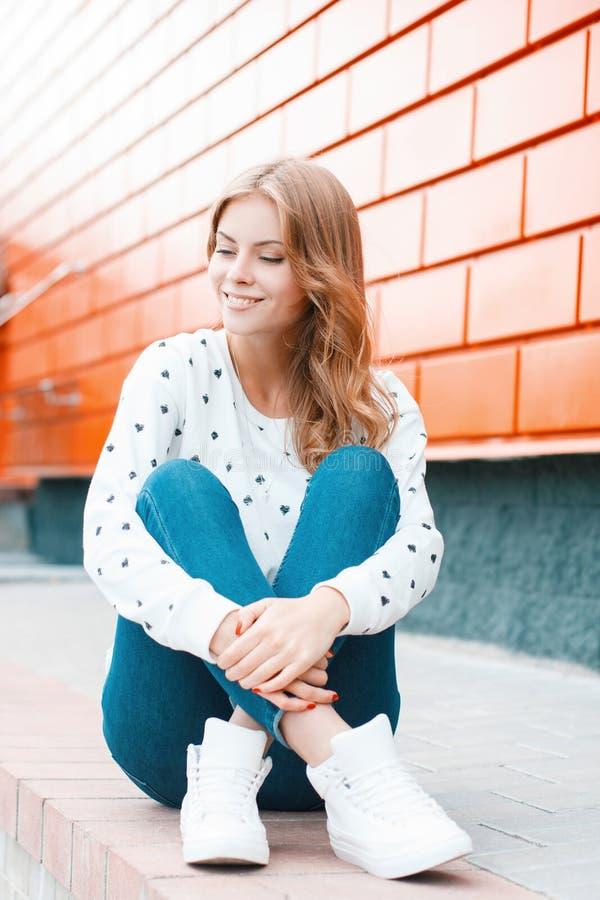 Η ελκυστική νέα εύθυμη γυναίκα στο εκλεκτής ποιότητας πουλόβερ στα καθιερώνοντα τη μόδα τζιν στα μοντέρνα πάνινα παπούτσια κάθετα στοκ εικόνα