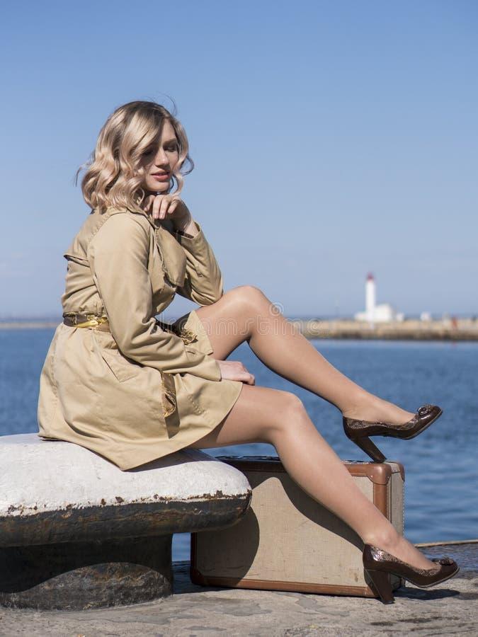 Η ελκυστική νέα ξανθή γυναίκα στην τάφρο με την εκλεκτής ποιότητας βαλίτσα κάθεται στην αποβάθρα Jacht στοκ εικόνα