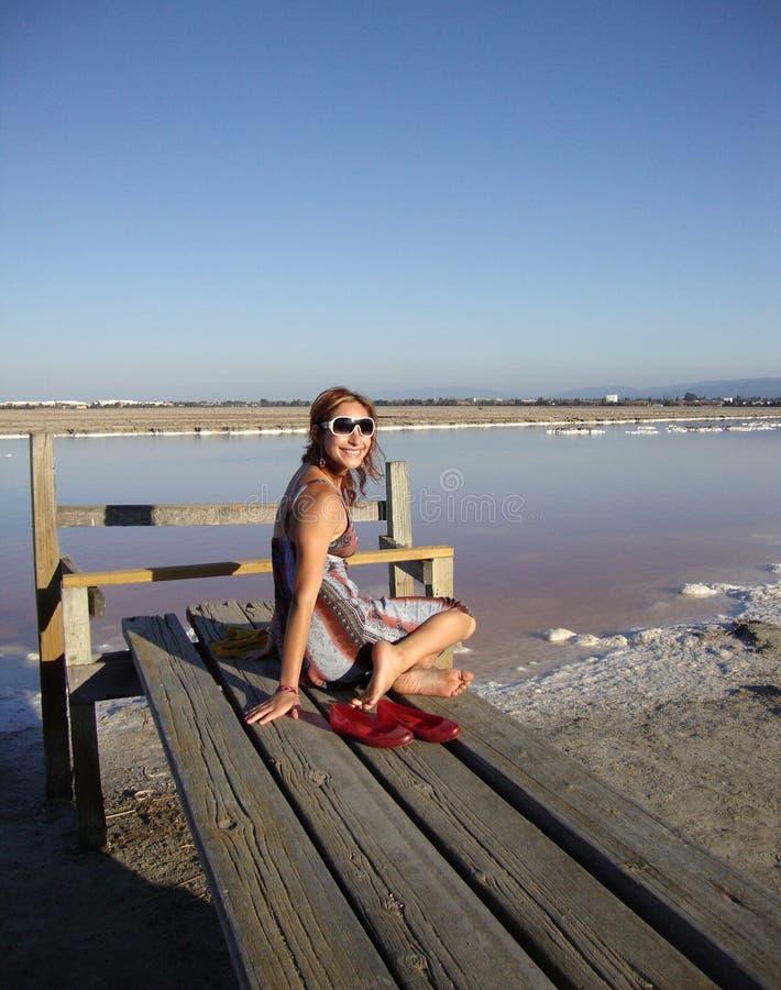 Η ελκυστική twentysomething κυρία κάθεται σε μια αποβάθρα στοκ φωτογραφίες