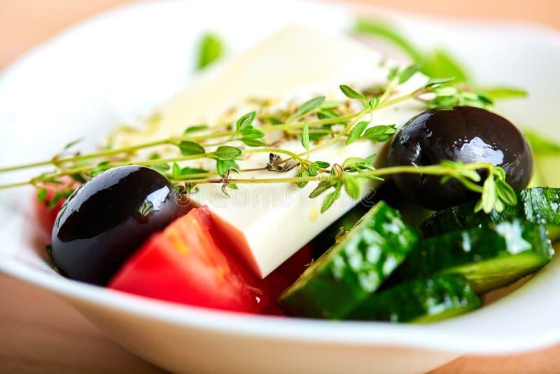 Η ελληνική σαλάτα είναι μια μεγάλη φέτα του μην τεμαχισμένου τυριού ξύλινο υπόβαθρο, κινηματογράφηση σε πρώτο πλάνο στοκ εικόνα με δικαίωμα ελεύθερης χρήσης