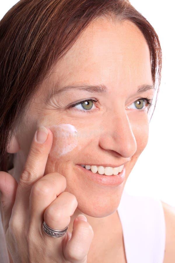 Η ενήλικη γυναίκα εφαρμόζει την κρέμα στο πρόσωπο στοκ εικόνες