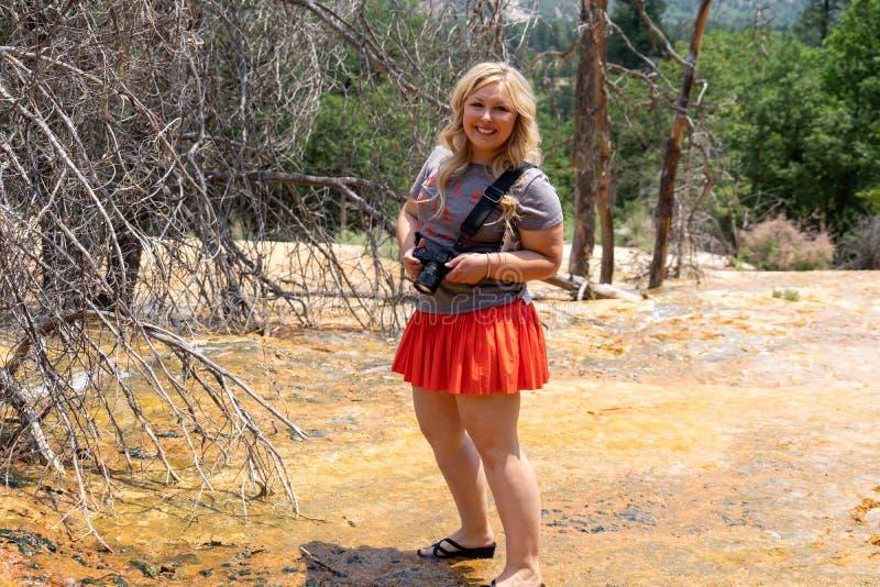 Η ενήλικη ξανθή θηλυκή γυναίκα στέκεται στο καυτό έδαφος στις καυτές ανοίξεις Pinkerton στο Κολοράντο στοκ εικόνες