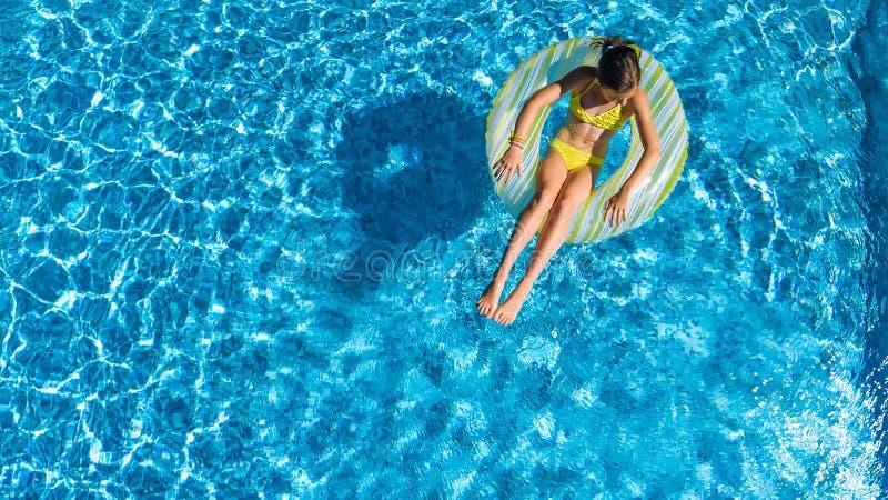 Η εναέρια άποψη κηφήνων του μικρού κοριτσιού στην πισίνα άνωθεν, παιδί κολυμπά διογκώσιμο doughnut δαχτυλιδιών, το παιδί έχει τη  στοκ φωτογραφίες