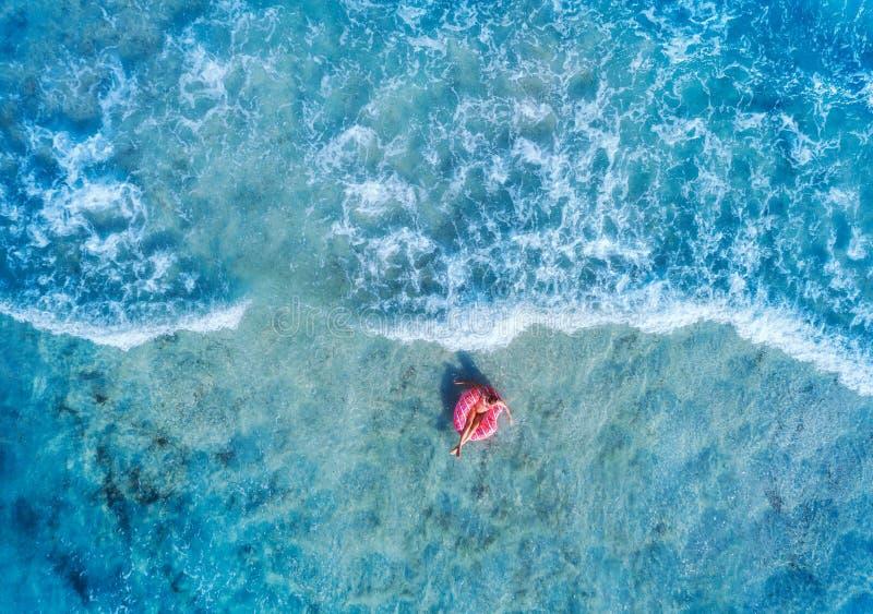 Η εναέρια άποψη μιας γυναίκας που κολυμπά με ρόδινο doughnut κολυμπά το δαχτυλίδι στοκ φωτογραφία με δικαίωμα ελεύθερης χρήσης