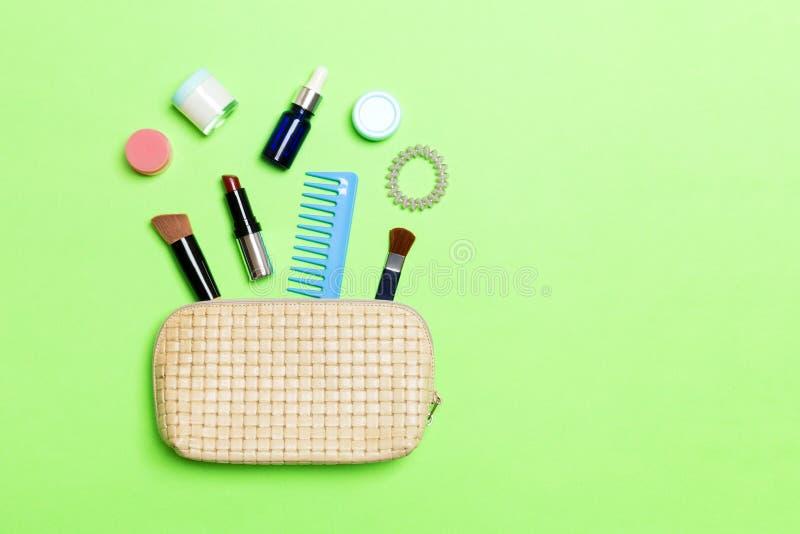 Η εναέρια άποψη μιας τσάντας καλλυντικών δέρματος με αποτελεί τα προϊόντα ομορφιάς ανατρέποντας έξω στο πράσινο υπόβαθρο Όμορφη έ στοκ εικόνα με δικαίωμα ελεύθερης χρήσης
