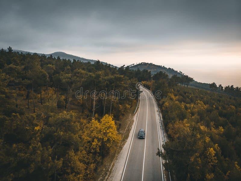 Η εναέρια άποψη του αυτοκινήτου στο δρόμο ασφάλτου βουνών φθινοπώρου, ταξίδι στην Ευρώπη στην έννοια μεταφορών, κηφήνας πυροβόλησ στοκ φωτογραφία με δικαίωμα ελεύθερης χρήσης