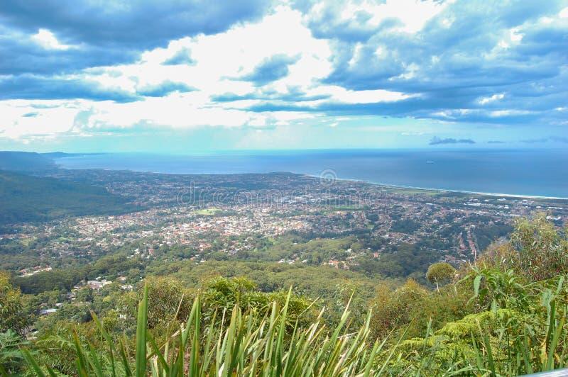 Η εναέρια άποψη Wollongong, Νότια Νέα Ουαλία από την κορυφή ενός βουνού στην Αυστραλία με το μαίνοντας δραματικό νεφελώδη ουρανό στοκ εικόνες
