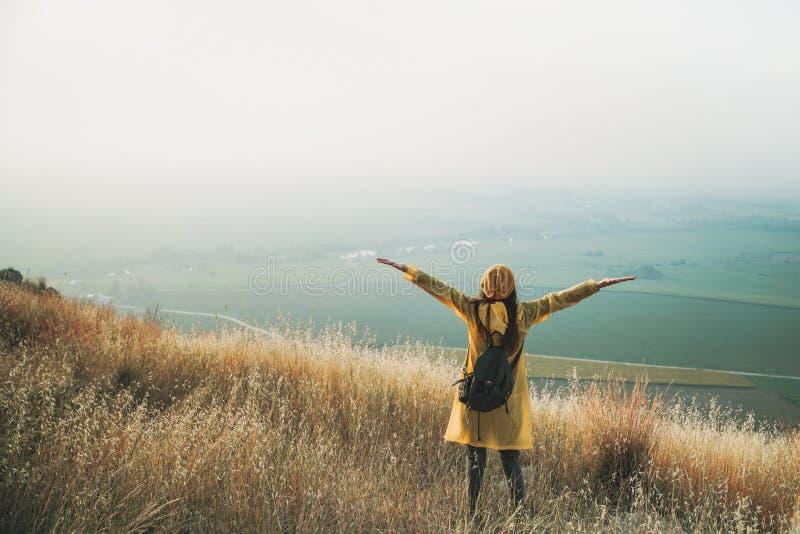 Η ενθαρρυντική γυναίκα απολαμβάνει την όμορφη θέα στην αιχμή βουνών στοκ εικόνα