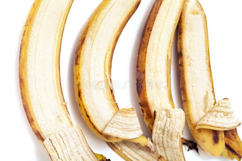Η εν μέρει ξεφλουδισμένη μπανάνα τέσσερα βρίσκεται στην οριζόντια σειρά στοκ εικόνες