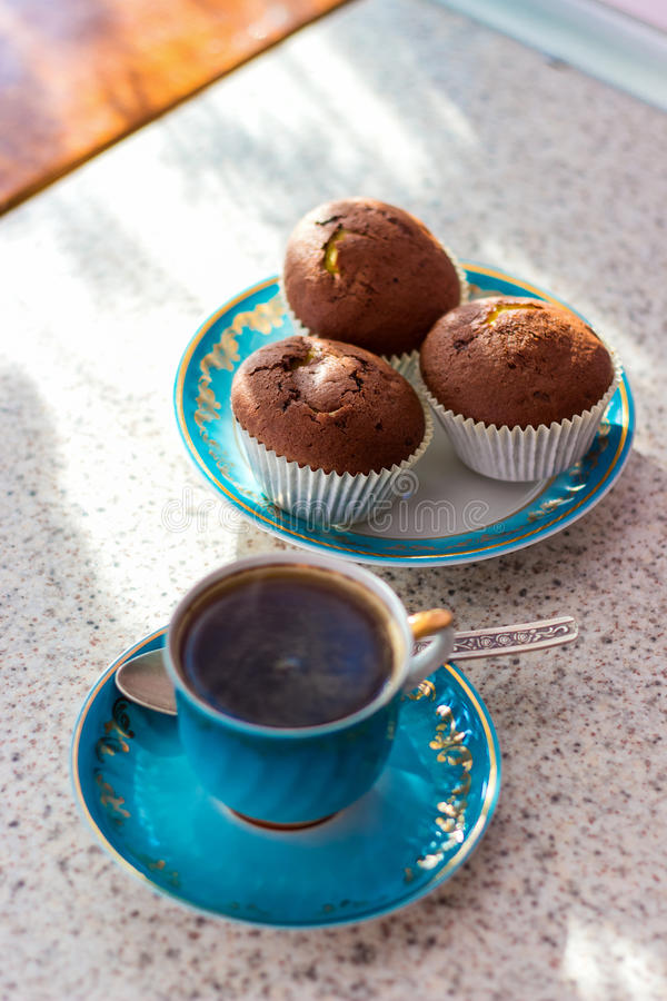 Η ενδυνάμωση του φλιτζανιού του καφέ με τα cupcakes είναι στον πίνακα για το πρόγευμα στοκ φωτογραφία
