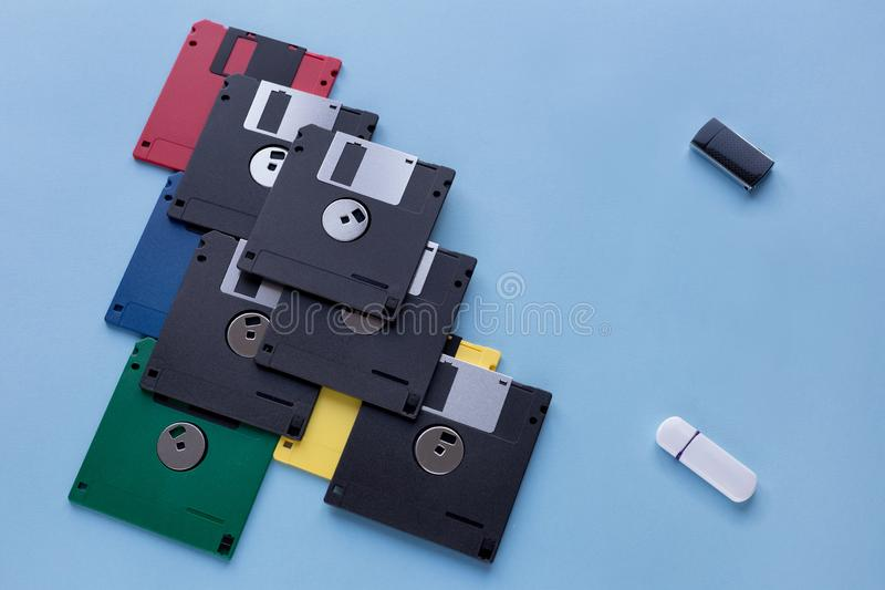 Η εξέλιξη της συσκευής αποθήκευσης ψηφιακών στοιχείων Δισκέτες εναντίον των μικρών κινήσεων λάμψης Απομονωμένος σε ένα μπλε υπόβα στοκ εικόνες