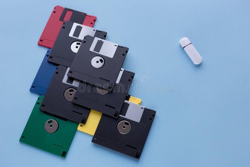 Η εξέλιξη της συσκευής αποθήκευσης ψηφιακών στοιχείων Δισκέτες εναντίον της μικρής κίνησης λάμψης Απομονωμένος σε ένα μπλε υπόβαθ στοκ φωτογραφίες με δικαίωμα ελεύθερης χρήσης