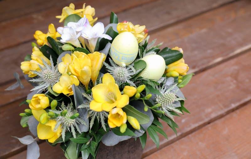 Η εορταστική ρύθμιση λουλουδιών του κίτρινου και άσπρου freesia ανθίζει και άλλες εγκαταστάσεις με τα αυγά Πάσχας που διακοσμούντ στοκ φωτογραφίες με δικαίωμα ελεύθερης χρήσης