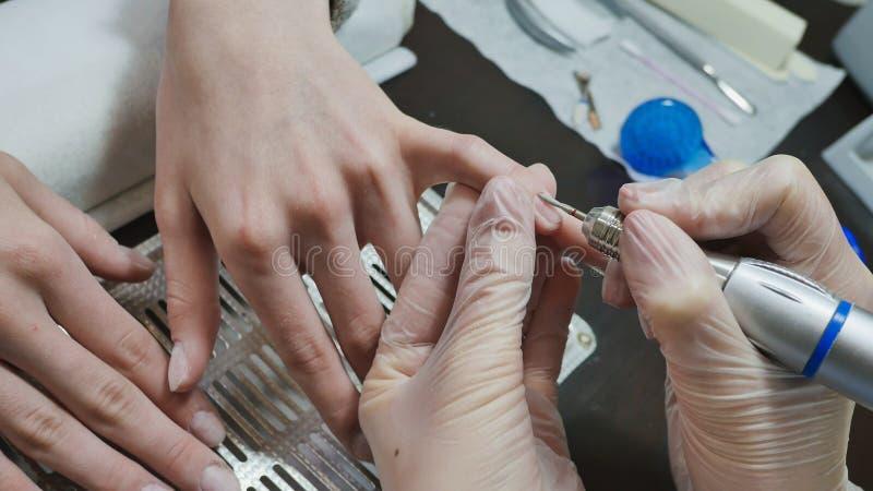 Η επεξεργασία επιδερμίδων είναι ένα από τα στάδια της επεξεργασίας της επιδερμίδας Χέρια γυναικών ` s στις διαδικασίες μανικιούρ στοκ φωτογραφίες