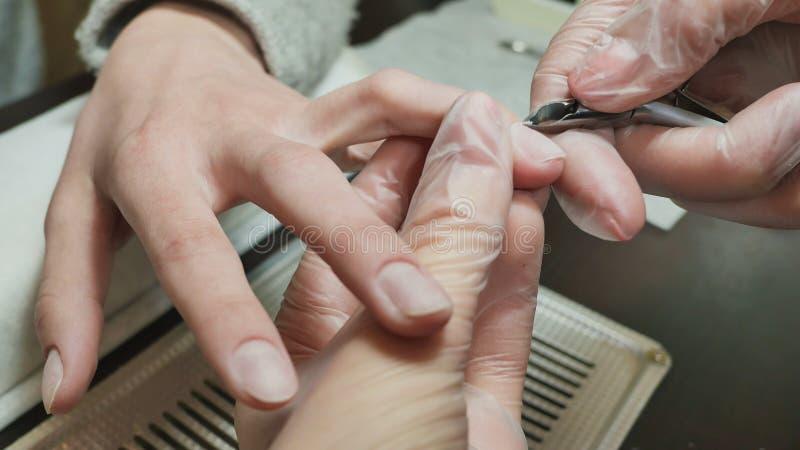 Η επεξεργασία επιδερμίδων είναι ένα από τα στάδια της επεξεργασίας της επιδερμίδας Χέρια γυναικών ` s στις διαδικασίες μανικιούρ στοκ φωτογραφία με δικαίωμα ελεύθερης χρήσης