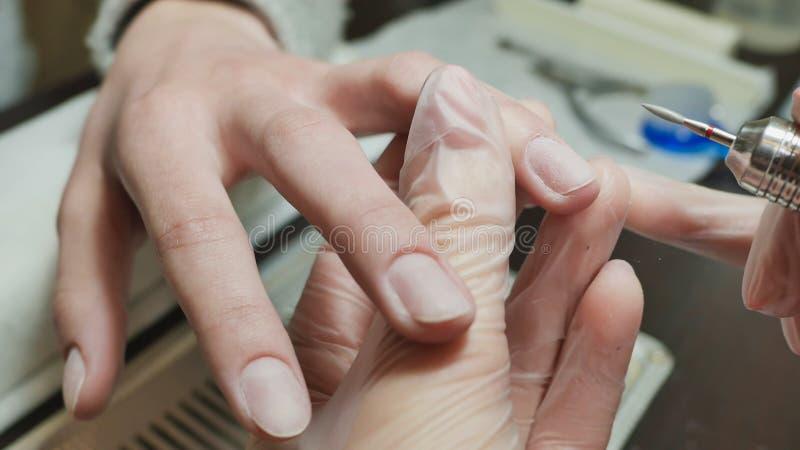 Η επεξεργασία επιδερμίδων είναι ένα από τα στάδια της επεξεργασίας της επιδερμίδας Χέρια γυναικών ` s στις διαδικασίες μανικιούρ στοκ εικόνες με δικαίωμα ελεύθερης χρήσης