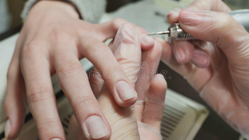 Η επεξεργασία επιδερμίδων είναι ένα από τα στάδια της επεξεργασίας της επιδερμίδας Χέρια γυναικών ` s στις διαδικασίες μανικιούρ στοκ εικόνα
