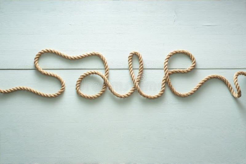 Η επιγραφή πώλησης γράφεται χρησιμοποιώντας ένα σχοινί φιαγμένο από γιούτα στοκ εικόνα