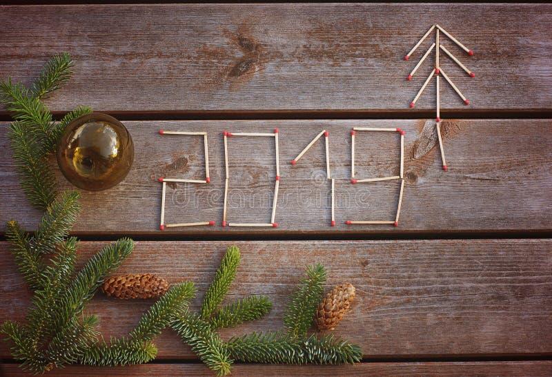 Η επιγραφή 2019, φιαγμένη επάνω από αντιστοιχίες σε ένα ξύλινο υπόβαθρο με έναν πράσινο κλάδο ενός χριστουγεννιάτικου δέντρου, θε στοκ εικόνες με δικαίωμα ελεύθερης χρήσης
