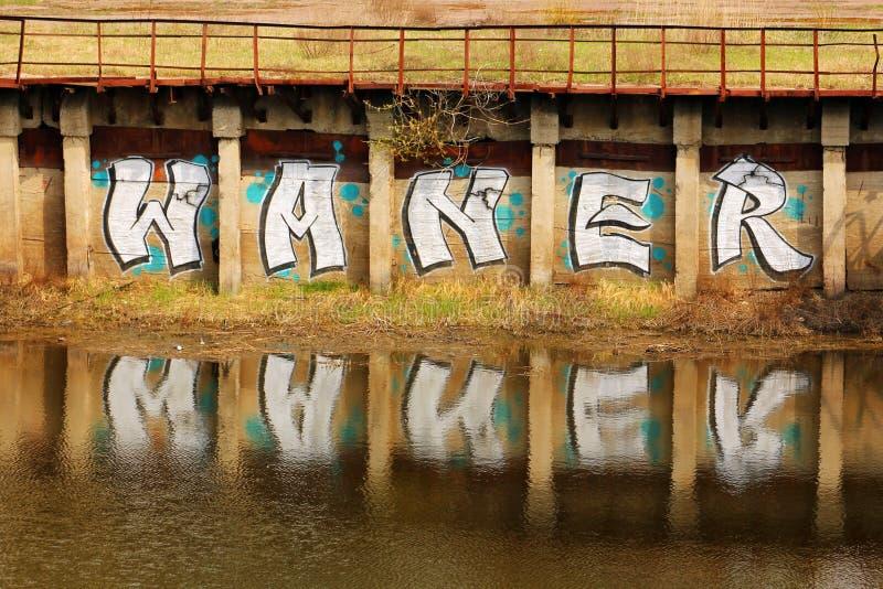 """Η επιγραφή """"Waner """"στον τοίχο κοντά στον ποταμό στοκ εικόνες"""