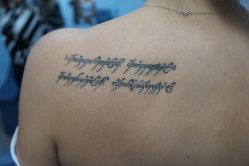 Η επιγραφή Elvish στην πλάτη του κοριτσιού στοκ εικόνα
