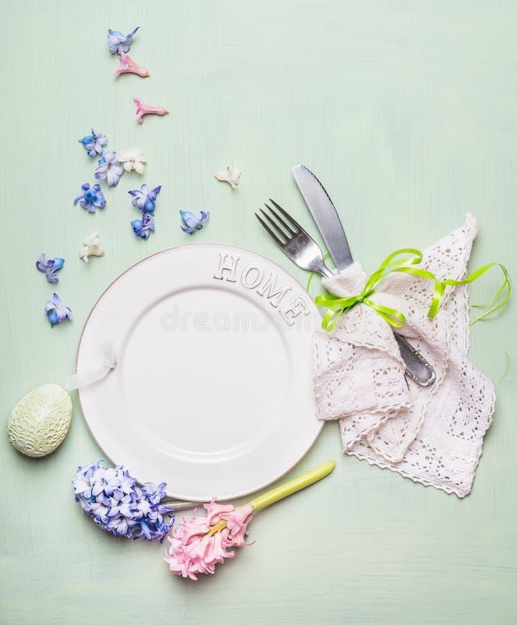 Η επιτραπέζια θέση Πάσχας που θέτει με το κενό πιάτο, υάκινθοι ανθίζει το αυγό διακοσμήσεων, μαχαιροπήρουνων και ντεκόρ στο ανοικ στοκ φωτογραφία με δικαίωμα ελεύθερης χρήσης