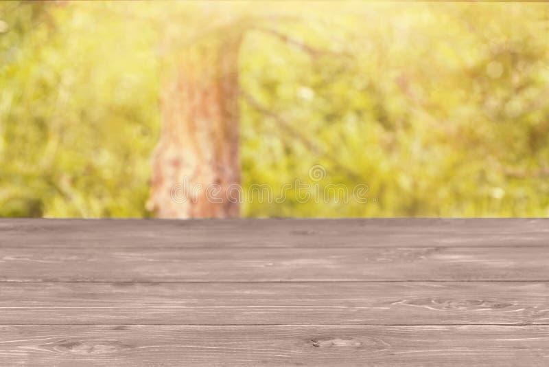 Η επιφάνεια του ξύλινου πίνακα και του θολωμένου κιτρινοπράσινου υποβάθρου Χλεύη προτύπων επάνω για την επίδειξη του προϊόντος στοκ εικόνα