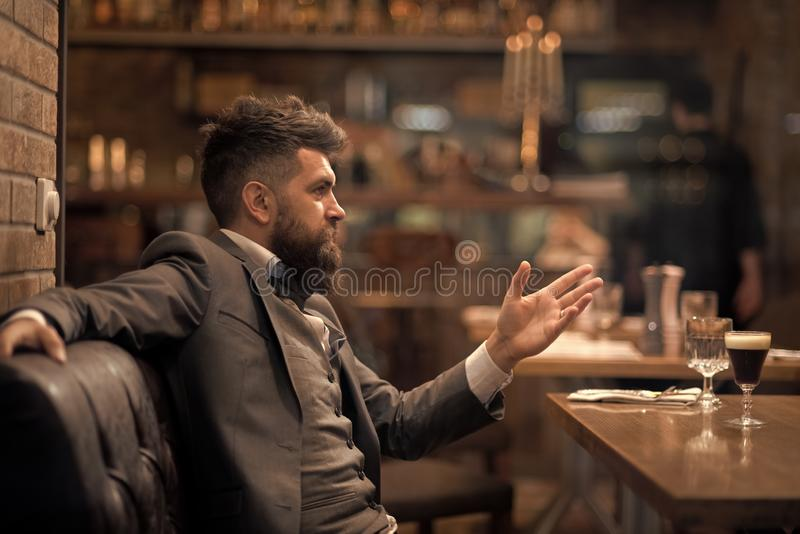 Η επιχείρηση συνεχίζεται και επικοινωνία Ο βέβαιος πελάτης φραγμών μιλά στον καφέ Επιχειρηματίας με τη μακριά γενειάδα στη λέσχη  στοκ φωτογραφία με δικαίωμα ελεύθερης χρήσης