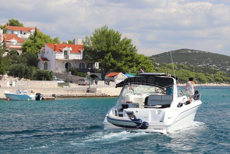 Η επιχείρηση των φίλων πανιά στα μικρά μηχανών γιοτ κατά μήκος της ακτής κοντά σε μια μικρή μεσογειακή πόλη Υπόλοιπο στο νερό στοκ εικόνα