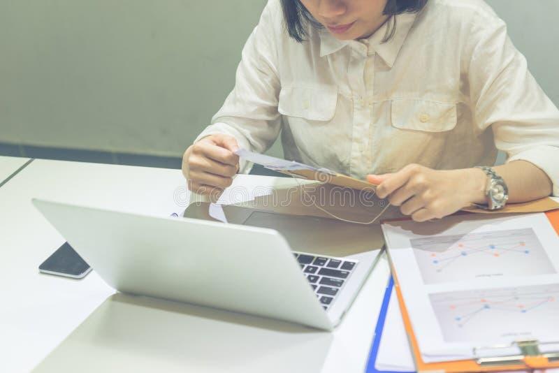 Η επιχειρηματίας ανοίγει μια επιστολή από τον καφετή φάκελο στοκ εικόνες με δικαίωμα ελεύθερης χρήσης