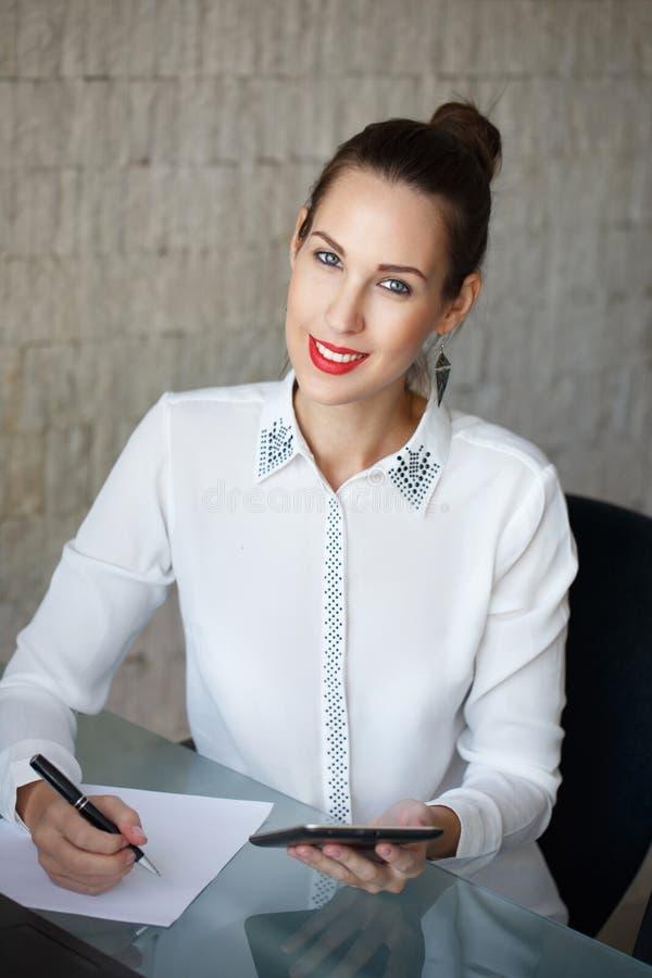 Η επιχειρηματίας γράφει στην κενή ταμπλέτα εγγράφου και εκμετάλλευσης στοκ εικόνα
