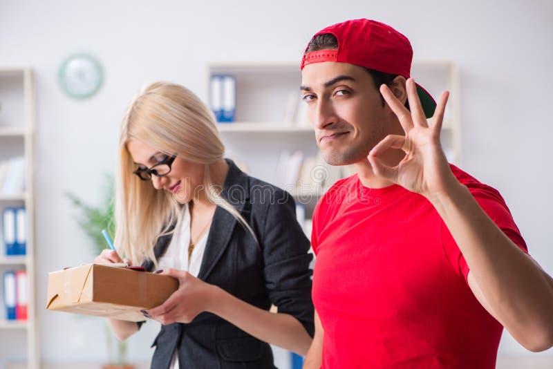 Η επιχειρηματίας γυναικών που λαμβάνει το δέμα ταχυδρομείου από τον αγγελιαφόρο στοκ φωτογραφία με δικαίωμα ελεύθερης χρήσης