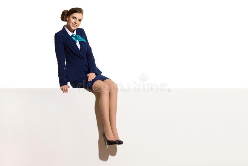 Η επιχειρηματίας κάθεται πάνω από το άσπρο έμβλημα στοκ εικόνες