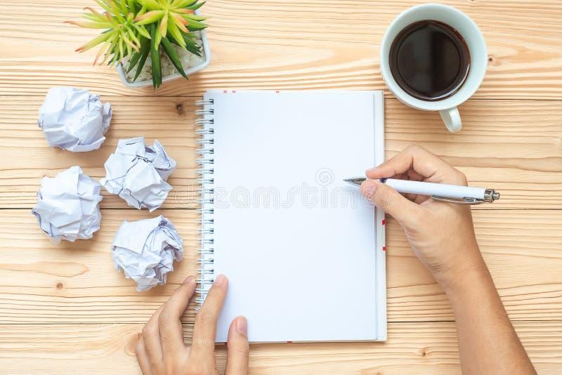 Η επιχειρηματίας που γράφουν με το σημειωματάριο, το θρυμματισμένο έγγραφο και ο μαύρος καφές κοιλαίνουν στον πίνακα Νέα έναρξη έ στοκ φωτογραφία