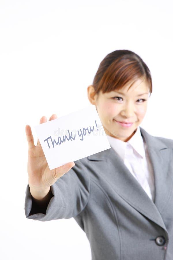 Η επιχειρηματίας που παρουσιάζει μια κάρτα με τη λέξη σας ευχαριστεί στοκ εικόνες